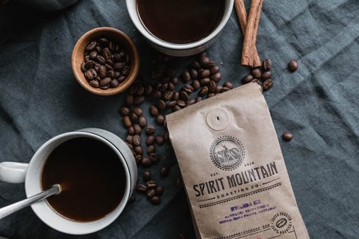 Cups of coffee, coffee beans, cinnamon sticks and a bag of Spirit Mountain Roasting Co. coffee lie on a table.